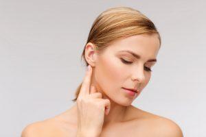 calm woman touching her ear
